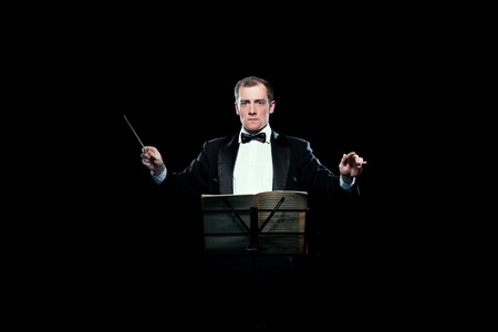 Studio photo of male music conductor holding his baton