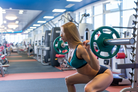 strength training: Beautiful young woman doing squats with barbell in gym Stock Photo