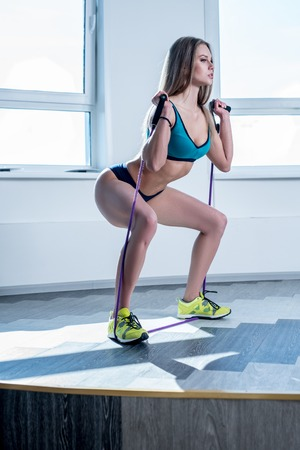 expander: In gym. Athletic woman doing squats using expander