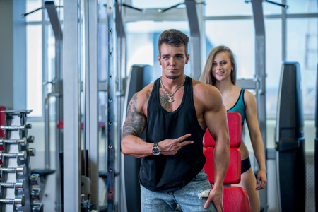 workout gym: Image of fitness instructor and pretty woman smiling in gym Stock Photo