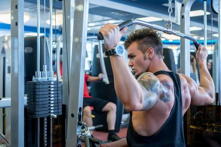 simulator: Back view of bodybuilder exercising on simulator in gym