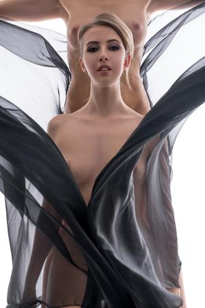 Studio photo of naked women posing with flying fabric