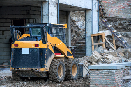 mini loader: Image of skid loader working on building construction Stock Photo