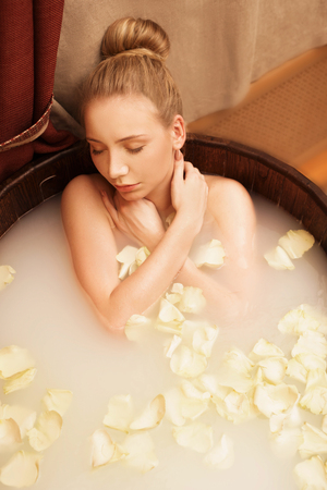 spa flower: Top view of girl enjoys relaxing bath with rose petals Stock Photo