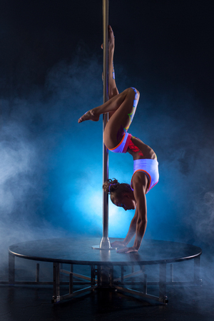Pole dance. Flexible girl posing while doing handstand Фото со стока