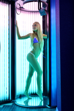 sunroom: Photo of leggy blonde tans in modern tanning booth Stock Photo