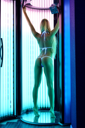 sunroom: Rear view of slender blond woman tans in tanning booth