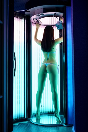 tans: Back view of slender brunette tans in tanning booth