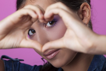 Portrait of young woman making heart with hands photo