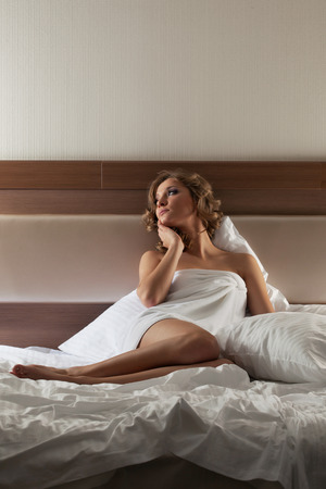 Portrait of pretty blonde woman sitting on bed photo