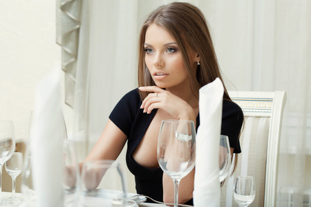 Portrait of seductive young woman posing in restaurant