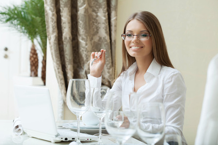 woman  glasses: Cheerful business woman works on PC at her lunch, close-up