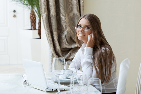 lady on phone: Smiling business lady talking on cell phone in restaurant Stock Photo