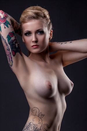 bare breast: Nude. Studio portrait of topless tattooed girl posing at camera Stock Photo