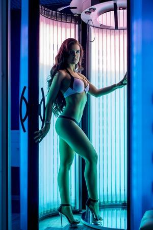 belle brune: Jolie femme posant tout en tans dans cabine de bronzage moderne Banque d'images