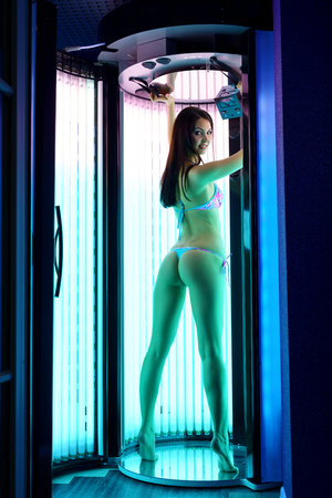 Sexy brunette posing while tanning in modern solarium