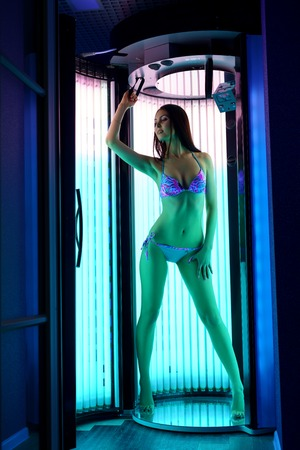 tans: Image of leggy brunette tans in modern tanning booth