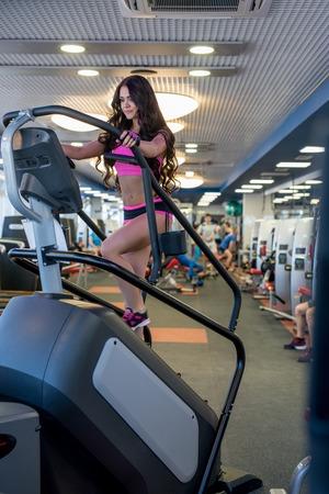 simulator: At gym. Image of beautiful woman exercising on simulator