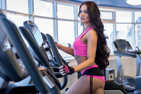 simulator: Cute brunette exercising on simulator in fitness center