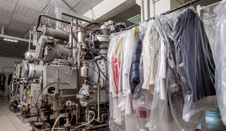 dry cleaning: Dry Cleaning. Image of modern equipment and clothing on hangers Stock Photo