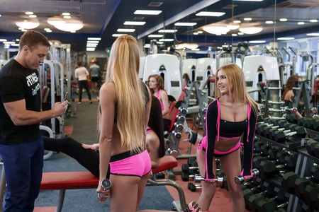 male body: Sporty girl posing coach during training with dumbbells