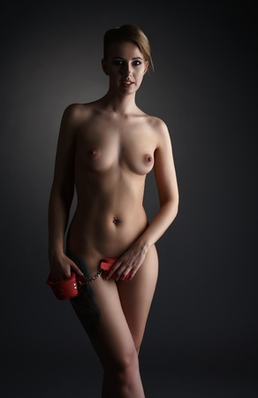 BDSM. Image of beautiful nude woman holds handcuffs