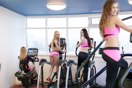 simulators: At fitness centre. Image of girls practicing on simulators