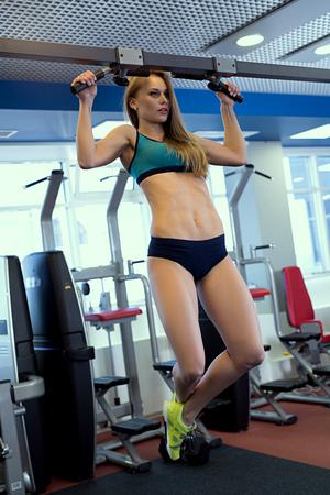 tightening: At gym. Image of beautiful woman tightening on bar Stock Photo
