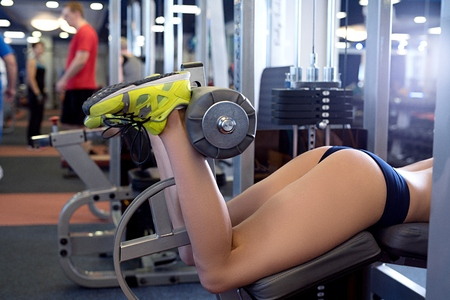 Close-up of sporty girl exercising on simulator at gym