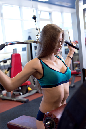builds: At gym. Girl builds her perfect body on simulator