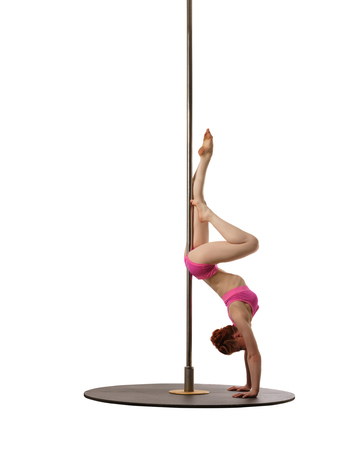 handstand: Pole dance. Red-haired woman doing handstand, isolated on white