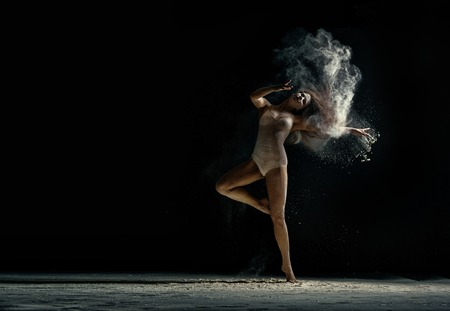 Amazing photo of graceful woman dancing with dust in studio