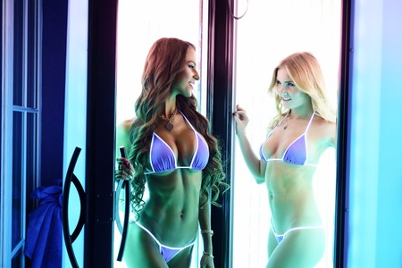 sunroom: Sexy young women posing in vertical tanning booth Stock Photo