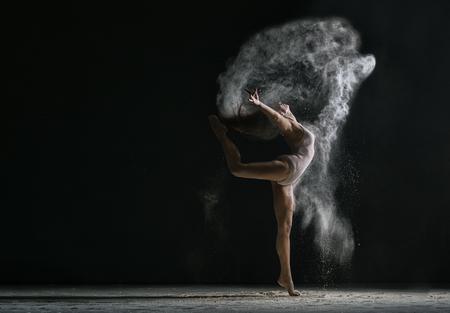 Concept. Flexible woman dancing in cloud of dust Stockfoto
