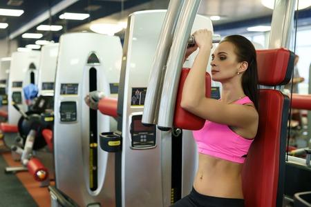 simulator: At gym. Beautiful young woman exercising on simulator Stock Photo