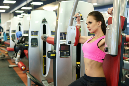 simulator: At fitness room. Image of sexy girl exercising on simulator