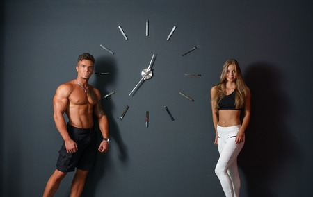 sexy women naked: Sport time. Concept. Attractive athletes posing with clock Stock Photo