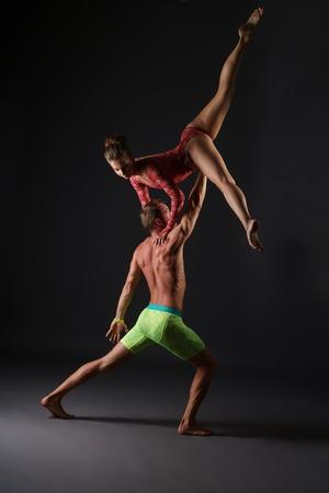 acrobatics: Acrobatics. Duet of gymnasts perform trick in studio