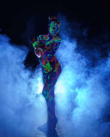 Nude girl with body art poses in UV light and smoke
