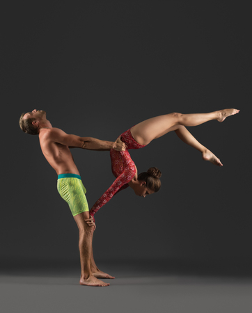 acrobatic: Acrobatic duo posing while practicing in studio, on gray background