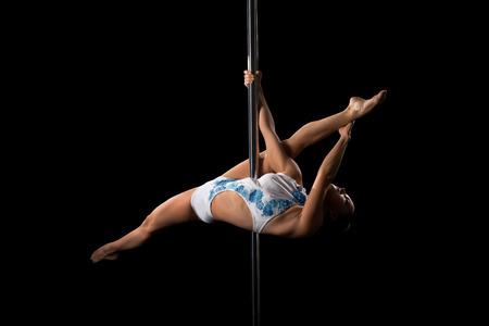 Image of flexible dancer performs gymnastic split on pylon