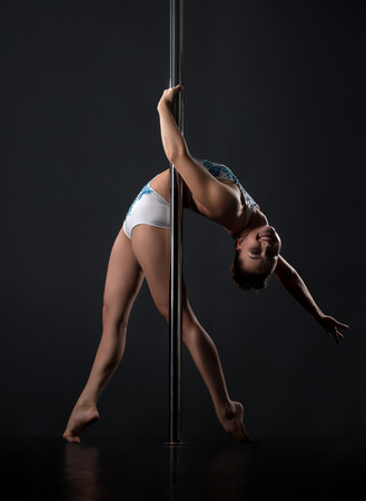Pole dance. Girl smiling at camera while bending her back