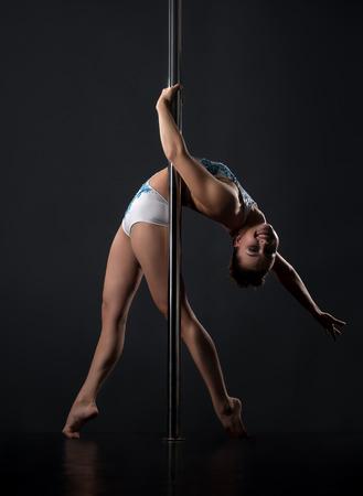 go go dancer: Pole dance. Girl smiling at camera while bending her back