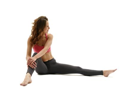 Smiling female athlete posing sitting and hugging her leg