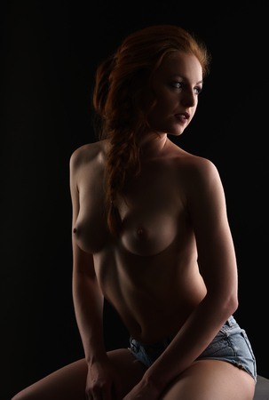 Beautiful breasts: Image of alluring red-haired woman posing nude at camera