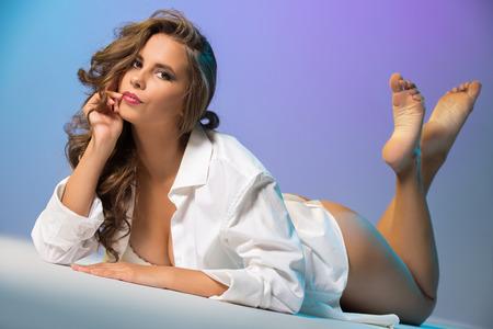 femmes nues sexy: Jeune femme brune coquetterie posant le mensonge dans le studio, sur fond bleu Banque d'images