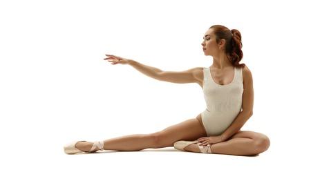 ballet clásico: Hermosa de la bailarina que se sienta con gracia. Aislado en el fondo blanco Foto de archivo