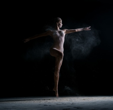 Female dancer jumping gracefully in cloud of powder