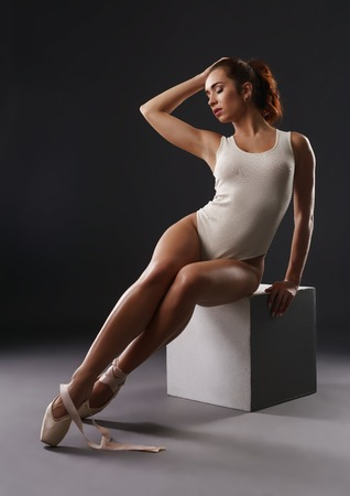 End of career concept. Ballerina sitting on cube and her pointe shoe untied