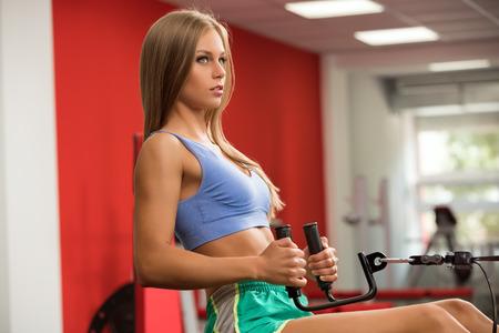 simulator: Fitness. Beautiful girl practicing on simulator in gym